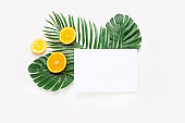 Creative hipster tropical leaves and orange fruit background with copy space on bright background. Tropical concept.