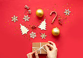 Flat lay composition. Woman hands and Christmas accessories and decorations on red background. top view, copy space