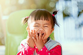 Cute asian baby girl laughing and playing peekaboo or hide and seek with fun