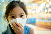 Cute asian child girl wearing protection mask to against air smog pollution with PM 2.5