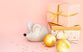 Christmas composition on a pink background. Boxes with gifts and the symbol of the Chinese New Year 2020 - Rat