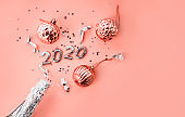 a bottle of champagne, Christmas toys and figures 2020. Christmas or New Year background, plain composition made of Xmas decorations and fir branches, flat lay, blank space for a greeting text.