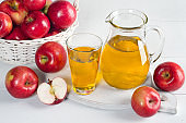 Apple juice in a decanter and a glass with apples on white table.