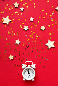 Flat lay composition. Alarm clock and Christmas decorations on red background. top view, copy space
