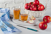 Red apples, juice in glasses, blue napkin and a knife on white table.