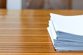 Stack of homework assignment on office wooden desk waiting to be managed and inspected for score. Pile of unfinished paperwork. Report and notebook papers stacked. Business and education concept.