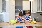 Happy child decorating meringue with blueberries . Child helping in kitchen