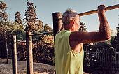 Old man senior doing push-up - sport activity at sunset