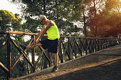 Old man senior doing stretching - sport activity at sunset at the park 60s 70s.