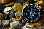 Compass on the pebbles and shell at riverside.