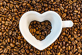 Heart shaped cup on coffee background