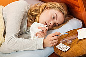 Sick woman in bed with thermometer and pills.