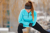 Winter workout. Girl wearing sportswear, stretching exercises.