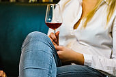 Woman in white shirt holding glass of wine
