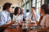 Business Colleagues Sitting Around Restaurant Table Enjoying Meal Together