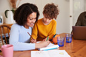 Mother Helping Son With Homework On Kitchen Table At Home