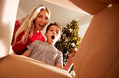 Mother And Son Opening Present On Christmas Morning Viewed From Inside Box