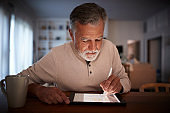 Senior Hispanic man sits at table using stylus and tablet computer at home in the evening, close up
