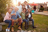 Portrait Of Mature Friends Sitting Around Fire And Making A Toast At Outdoor Campsite Bar