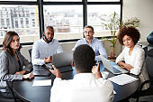 Corporate business people in a meeting room listening to a colleague speaking, elevated view