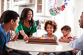 Close up of three generation family sitting together at the kitchen table celebrating the pre-teen daughterâ'u20acs birthday with a birthday cake