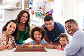 Three generation family mixed race family gathered in the kitchen celebrating a birthday together, looking to camera smiling