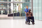 Female Nurse Wearing Scrubs Wheeling Patient In Wheelchair Through Lobby Of Modern Hospital Building