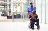 Male Nurse Wearing Scrubs Wheeling Patient In Wheelchair Through Lobby Of Modern Hospital Building