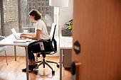 Businesswoman Sitting At Desk Working On Laptop In Modern Office Viewed Through Door Way