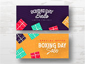 Boxing Day Sale banner design decorated with gift boxes in two color option on white wooden background.