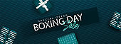 Website header or banner design with Boxing Day Sale text and top view of gift boxes decorated on green striped background.