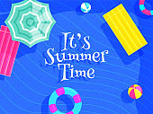 Stylish text It's Summer Time with top view of beach elements such as ball, lifebuoy and umbrella on blue wavy strip background.