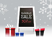Holiday Sale text in painting board with 50% discount offer and gift boxes on winter snow background. Can be used as banner or poster design.