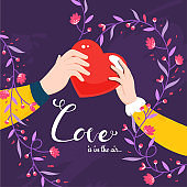 Couple Hand holding Red Heart with Given Message as Love Is In The Air and Floral Motif Decorated on Purple Background.