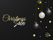 Christmas Sale Poster Design Decorated with Hanging Baubles, Golden Stars and Snowflakes on Black Background.
