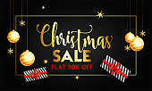 Christmas Sale banner or poster design with 50% discount offer, hanging baubles and gift boxes on black background.
