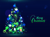Green calligraphy text Merry Christmas and creative Xmas tree made by bokeh effect on blue background can be used as greeting card design.