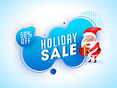 Holiday Sale banner or poster design with 50% discount offer and illustration of santa claus holding gift box on abstract background.