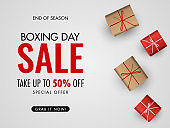 Boxing Day Sale poster or banner design with 50% discount offer and top view of gift boxes on white background.