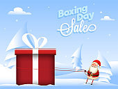 Boxing Day Sale poster design with paper cut xmas tree and illustration of santa pulling rope of gift box on snowy background.