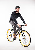 Portrait of a hipster beard man riding on bicycle over gray background