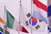 Indian, Italian, South Korean, Luxembourger Flags Against Cloudy Sky