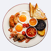 Full fry up English breakfast with fried eggs, sausages, bacon, black pudding, beans and toasts