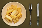 french fries on a beige plate on a brown background.fast food top view.