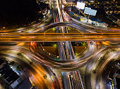 Aerial view of highway junctions with roundabout. Bridge roads shape circle in structure of architecture and transportation concept. Top view. Urban city, Bangkok at night, Thailand.