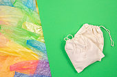 Many multicolored plastic bags with one eco natural reusable bag for shopping on green background. Zero waste, eco friendly, sustainability lifestyle, no plastic concept