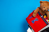 Donation box with clothing, books, children toys on blue background. Top view