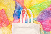 Many multicolored plastic bags with one eco natural reusable shopping bag background. Zero waste, eco friendly, sustainability lifestyle, no plastic concept