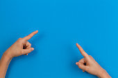 Kid hands pointing to something on blue background
