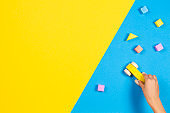 Child hands playing with wooden toy car and colourful building blocks on blue and yellow background, top view